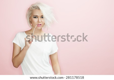 Portrait fashion blond model with sunglasses in hand on a pink background - stock photo