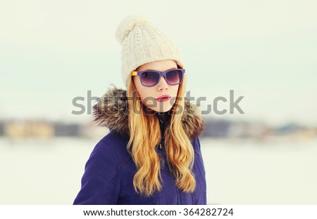 Portrait fashion blonde girl wearing a jacket, hat and sunglasses outdoors - stock photo