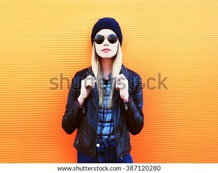 Portrait fashion blonde woman in rock black style over orange background - stock photo