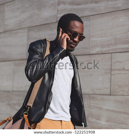 Portrait fashion confident young african man talking on smartphone in evening city