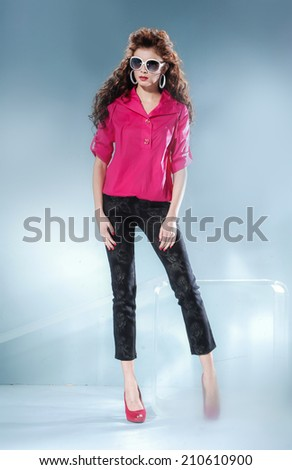 portrait fashion model wearing modern sunglasses posing in studio - stock photo