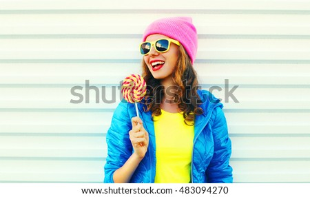 Portrait fashion pretty cool laughing woman with lollipop in colorful clothes over white background wearing a pink hat yellow sunglasses and blue jacket