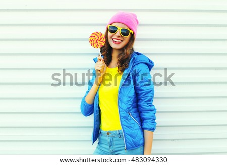 Portrait fashion pretty cool smiling woman with lollipop in colorful clothes over white background, wearing a pink hat, yellow sunglasses and blue jacket