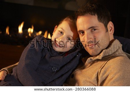 Portrait father and daughter by firelight - stock photo