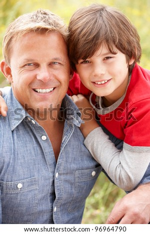 Portrait father and son outdoors - stock photo