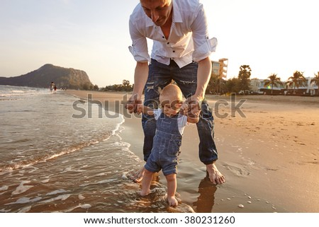 Portrait father with toddler son playing on the beach - stock photo