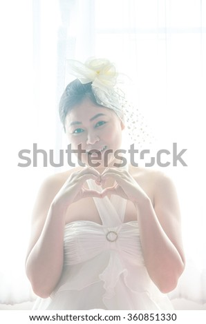 portrait female bride with hands shaping a heart symbol on window white background (Filter bright pink tone) - stock photo