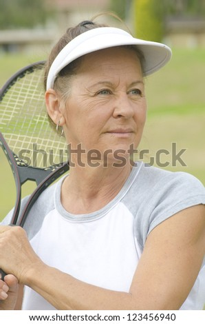 Portrait Fit and active Attractive looking middle aged woman with tennis racket, confident and happy, on blurred green background outdoor. - stock photo