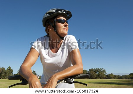 Portrait Fit and healthy looking mature woman in her fifties riding her bike, isolated with park and blue sky as background and copy space. - stock photo