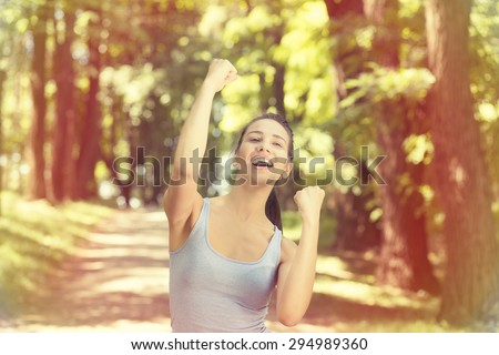 Portrait fit female fitness runner joyful and excited after running. Woman pumping fists. Success in sport training wellness concept. Positive face expression emotion  - stock photo