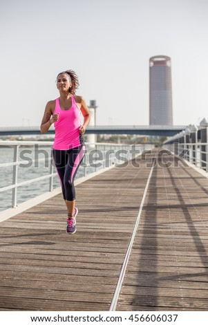 Portrait format picture of a young woman running with a skyscraper behind