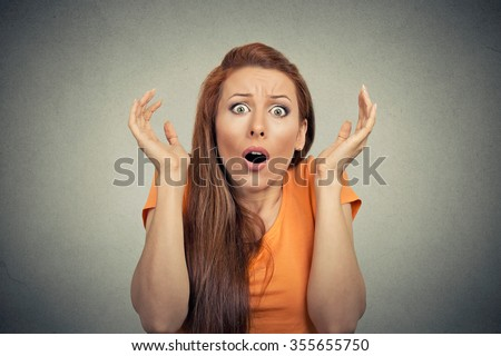 Portrait frightened shocked scared woman looking at camera isolated on gray wall background. Human emotion facial expression body language unexpected reaction - stock photo