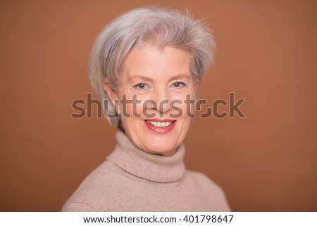 Portrait from a senior woman in front of brown background