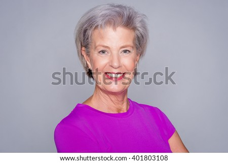 Portrait from a sportive senior woman in front of gray background - stock photo