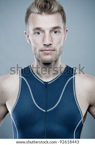 Portrait from a young sportsman in front of blue background - stock photo