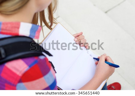 Portrait from above of a girl writing a to do list in book - stock photo