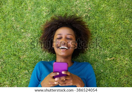 Portrait from above of a laughing woman lying on grass with cell phone - stock photo