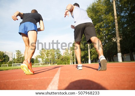 Portrait from behind of two running sports men