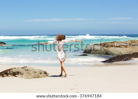 Portrait from behind of young woman walking to the water on the beach - stock photo