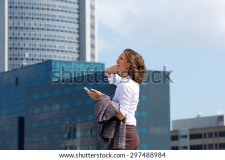 Portrait front he side of a smiling business woman walking in the city with mobile phone - stock photo