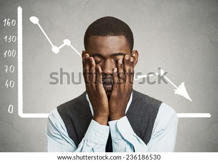 Portrait frustrated stressed business man desperate with financial market chart graphic going down on grey office wall background. Poor economy financial crisis concept. Face expression, emotion - stock photo