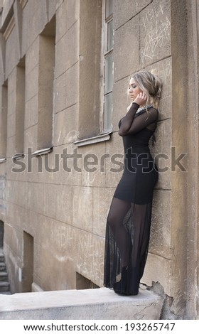 Portrait full length of Beautiful young adult caucasian woman standing, based on abandoned old concrete wall Blond cute girl looking down in black transparent fashion dress Copy space for inscription