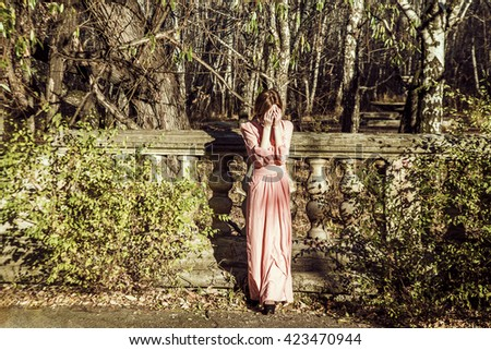 Portrait full length of Beautiful young adult slim caucasian woman stand against abandoned old fence. Redhead cute girl wear long fashion dress. hands on face and close the eyes - stock photo