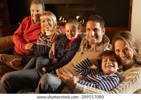 Portrait 3 generation family at home by firelight - stock photo