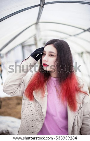 Portrait girl with half red hair in snow. Russian winter asian model.