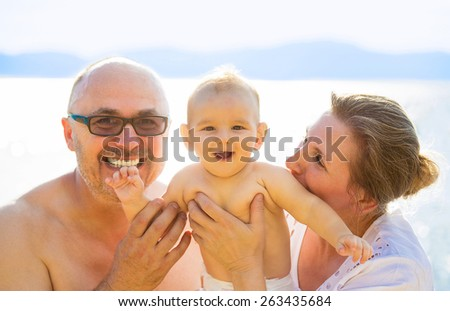 Portrait Grandparents And little Grandchild Enjoying Beach Holiday  - stock photo