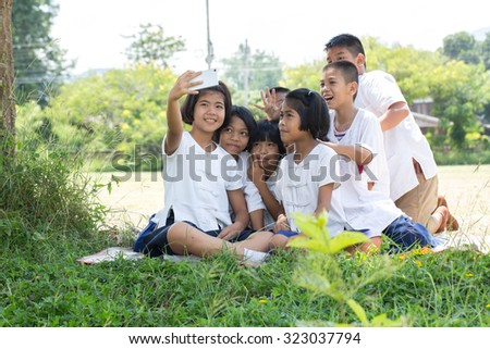 Portrait group  of childrens taking a selfie in the field under the tree
