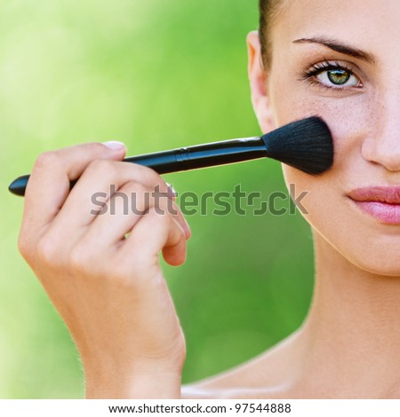 portrait half face of beautiful dark-haired sexy girls with makeup brush in hand on green background
