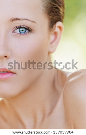 Portrait half of charming young woman close up with bared shoulders, against background of summer green park. - stock photo