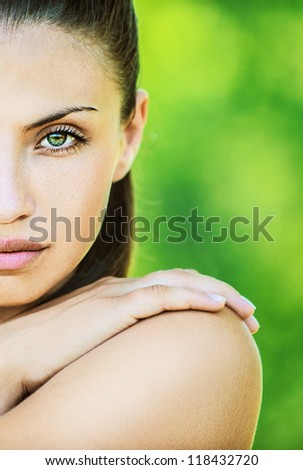 Portrait half of face young beautiful woman with bare shoulders crossed her arms, on green background summer nature.