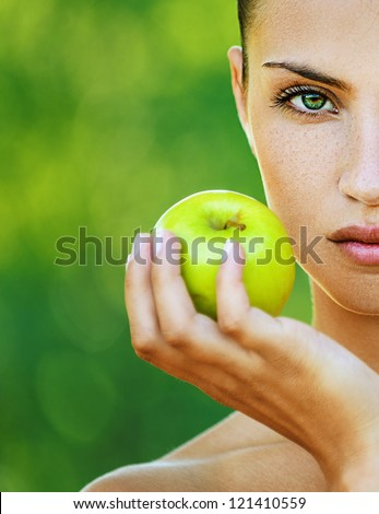 Portrait half of face young beautiful woman with bare shoulders holding an apple, on green background summer nature.