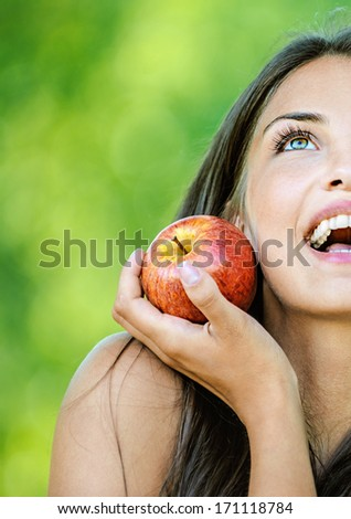 Portrait half of face young beautiful woman with bare shoulders holding an red apple and smiling, on green background summer nature. - stock photo