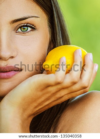 Portrait half of face young beautiful woman with bare shoulders holding lemon yellow, on green background summer nature. - stock photo
