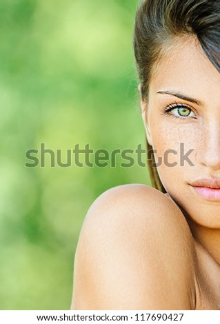 Portrait half of face young beautiful woman with bare shoulders , on green background summer nature.