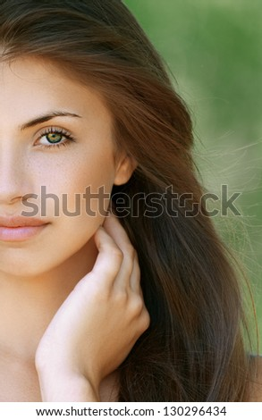 Portrait half of nice dark-haired young woman, against background of summer green park. - stock photo