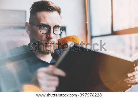 Portrait handsome bearded businessman wearing glasses,black shirt.Man sitting in vintage chair modern loft studio, reading book and relaxing.Time break. Blurred background.Horizontal, film effect.  - stock photo