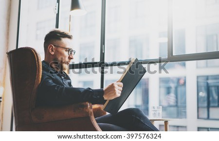 Portrait handsome bearded businessman wearing glasses,black shirt.Man sitting in vintage chair modern loft studio, reading book and relaxing. Blurred background.Horizontal, film effect.  - stock photo