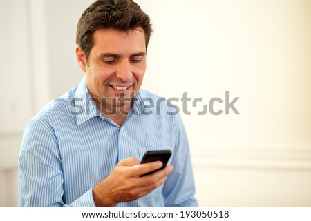 Portrait handsome businessman texting with his cellphone while smiling on closeup background - copyspace - stock photo