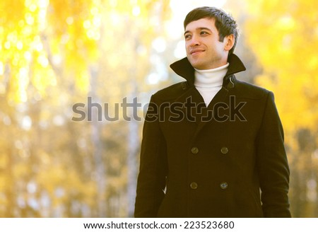Portrait handsome smiling man in coat outdoors in autumn park - stock photo