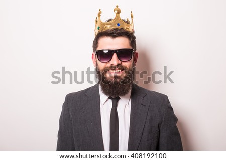 Portrait handsome young cheerful man in suit with crown looking at camera with smile while standing against white background - stock photo