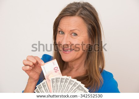 Portrait happy attractive mature woman holding Euro and US dollar notes, isolated, bright background. - stock photo