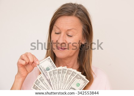 Portrait happy attractive mature woman presenting US dollar money, isolated, bright background. - stock photo