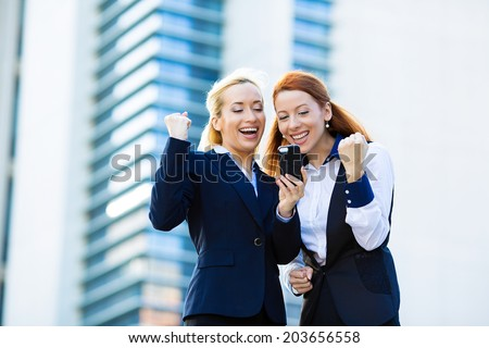Portrait happy business women, arms raised up, partners receiving news on mobile phone, looking at smartphone reading text message pumping fist celebrating success - stock photo