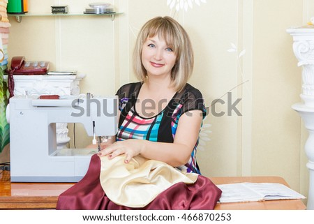 Portrait happy charming adult woman seamstress thinking and working in studio