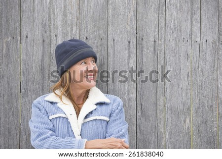Portrait happy confident attractive mature woman outdoor, wearing warm bonnet and wool jacket, timber wall background, copy space. - stock photo