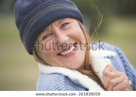 Portrait happy confident smiling attractive mature woman outdoor, wearing warm bonnet and wool jacket, blurred green background. - stock photo